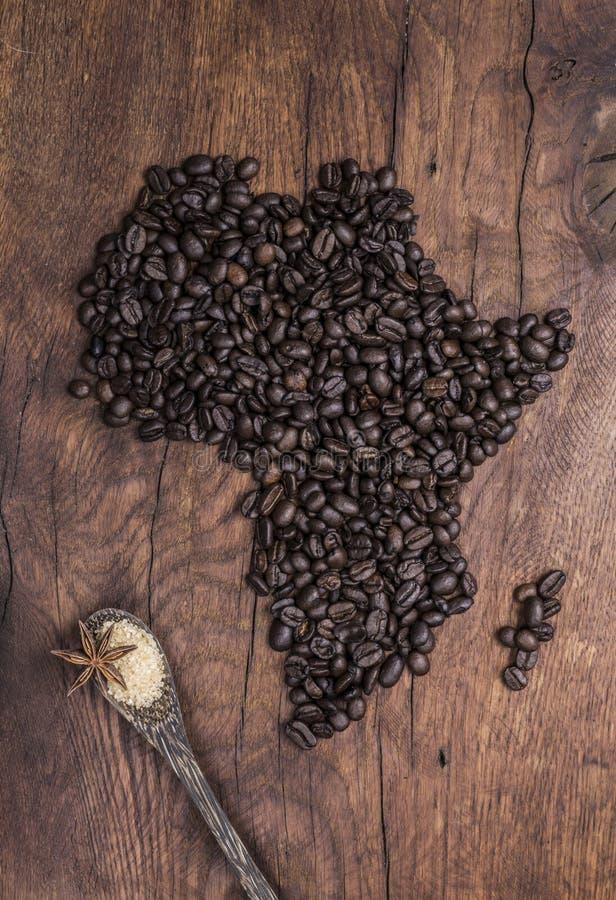 Geroosterde die koffiebonen in de vorm van Afrika op oud hout worden geschikt stock afbeelding