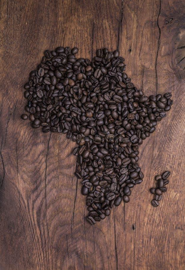 Geroosterde die koffiebonen in de vorm van Afrika op oud hout worden geschikt royalty-vrije stock fotografie