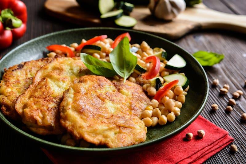 Geroosterde die varkensvleeskoteletten in gediende kaas en broodkruimels, met kekers en groente met een laag worden bedekt stock afbeeldingen
