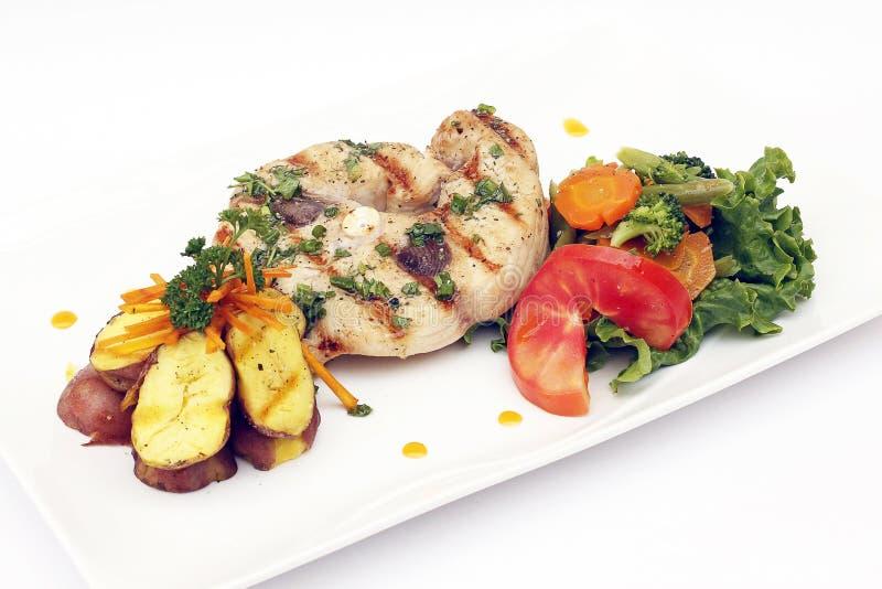 Geroosterde die Vissen met aardappels, wortelen en tomaten worden gediend Peruviaanse schotel stock afbeeldingen