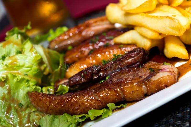 Geroosterde eend met frieten, aardappels, gekarameliseerd, en Salade royalty-vrije stock foto's