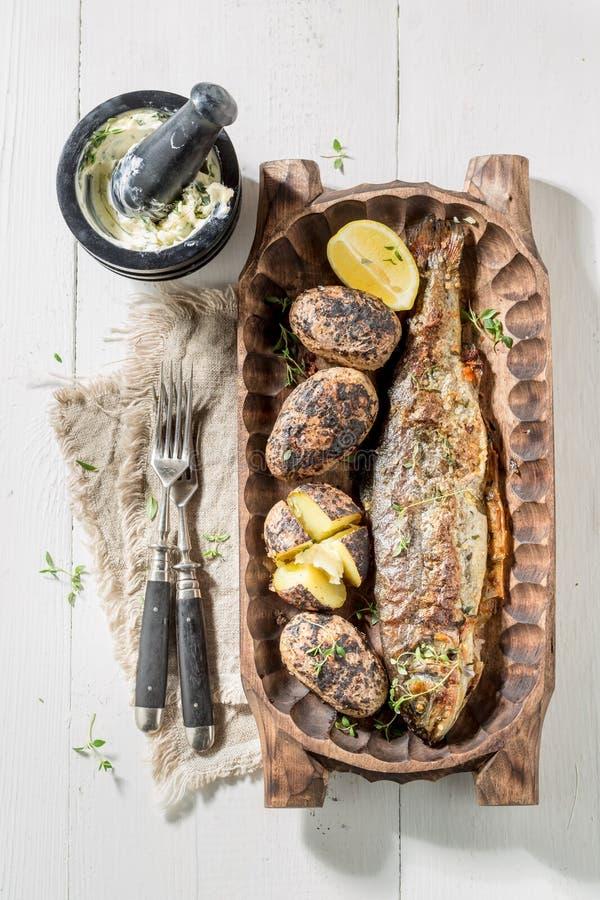 Geroosterde forelvissen en aardappels met aardappel en boter royalty-vrije stock foto