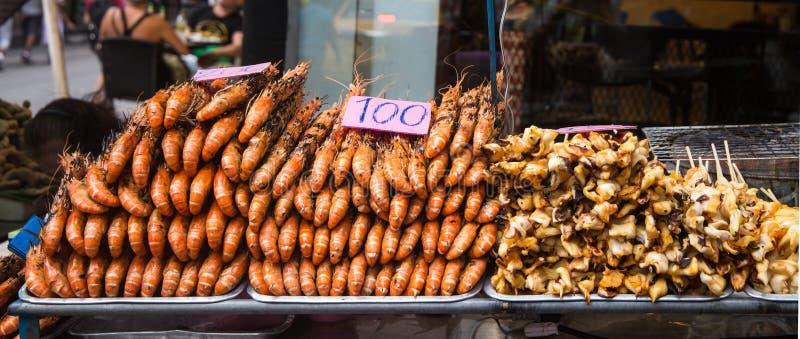 Geroosterde garnalen en pijlinktvissen op bbq voor verkoop in Bangkok, Thailand stock foto's