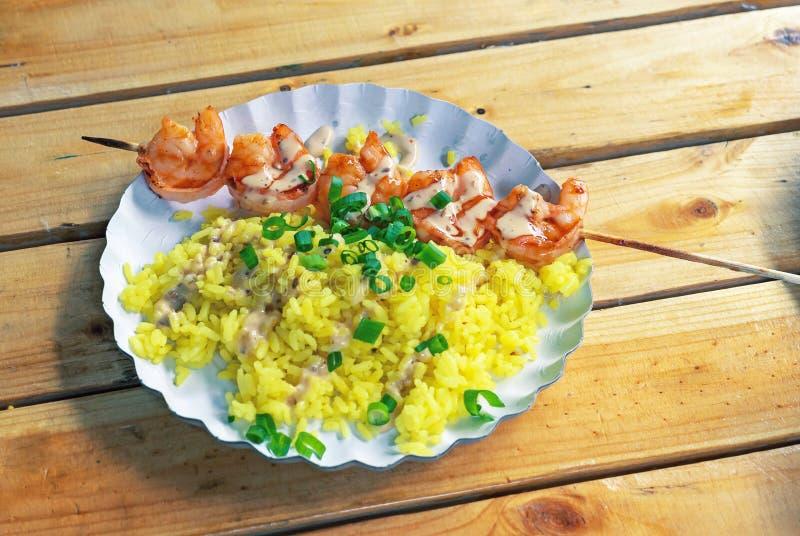 Geroosterde garnalen en rijst met kerriesaus Indonesische keuken met zeevruchten stock afbeeldingen