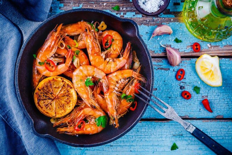 Geroosterde garnalen met peterselie, Spaanse peperpeper, knoflook en citroen stock foto's