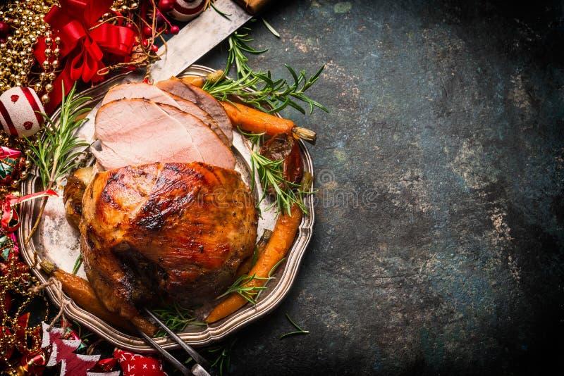 Geroosterde gesneden Kerstmisham op plaat met vork, mes en feestelijke decoratie op donkere rustieke achtergrond royalty-vrije stock afbeelding