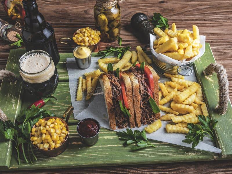 Geroosterde getrokken rundvleessandwich, toost, frieten, saus, donker bier, graan op een houten dienblad stock afbeelding