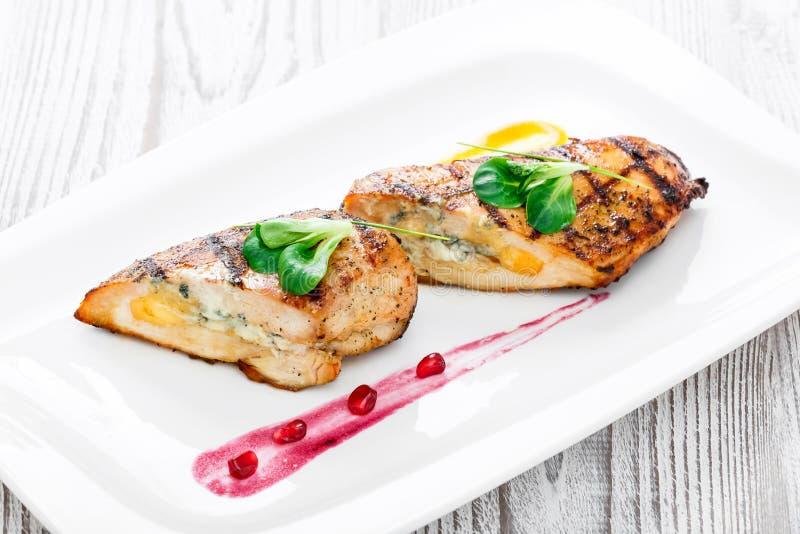 Geroosterde gevulde kippenborst met dicht omhoog kaas en eieren op plaat op houten achtergrond royalty-vrije stock foto