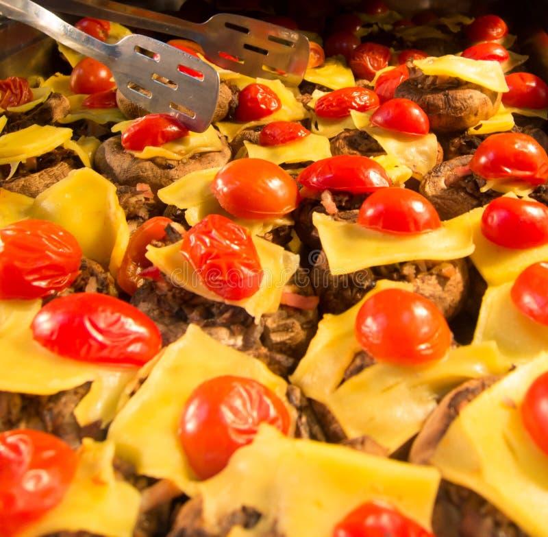 Geroosterde gevulde paddestoelen met gedrukte kaas en kersentomaten stock afbeelding