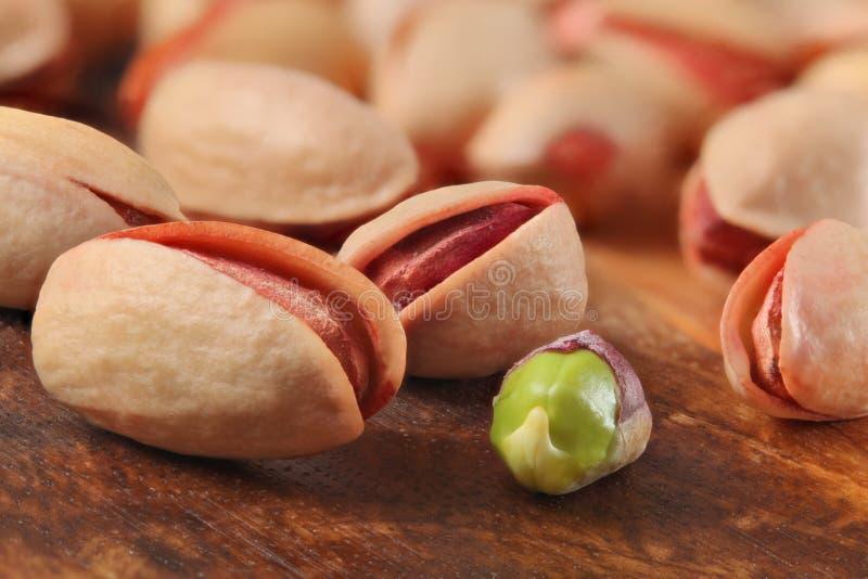 Geroosterde gezouten Turkse rode pistaches, één van hen pelden, groen zaad zichtbaar, op houten raad close-updetail stock fotografie