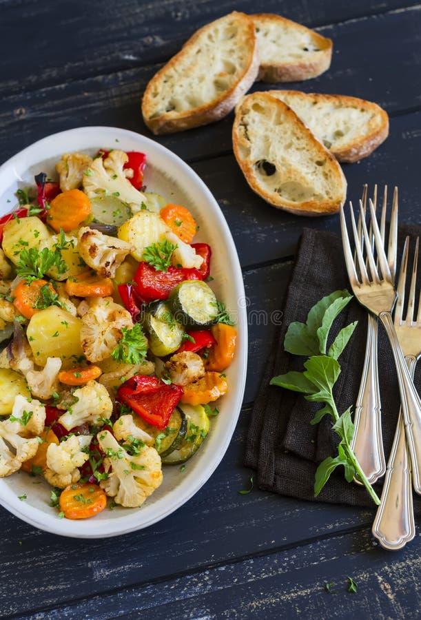 Geroosterde groenten - courgette, bloemkool, aardappels, wortelen, uien, peper, op een ovale schotel stock foto's