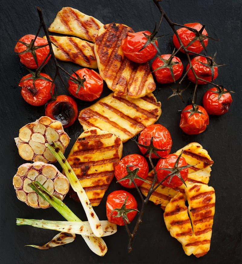 Geroosterde groenten met halloumikaas op een zwarte achtergrond stock foto