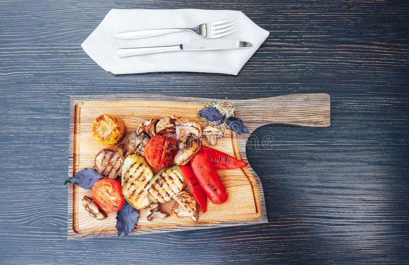 Geroosterde groenten op scherpe raad op donkere houten achtergrond Geroosterde Groentenmengeling stock fotografie