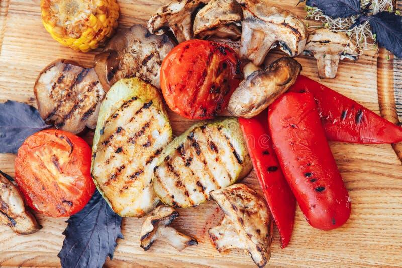 Geroosterde groenten op scherpe raad op donkere houten achtergrond Geroosterde Groentenmengeling Hoogste mening stock afbeeldingen