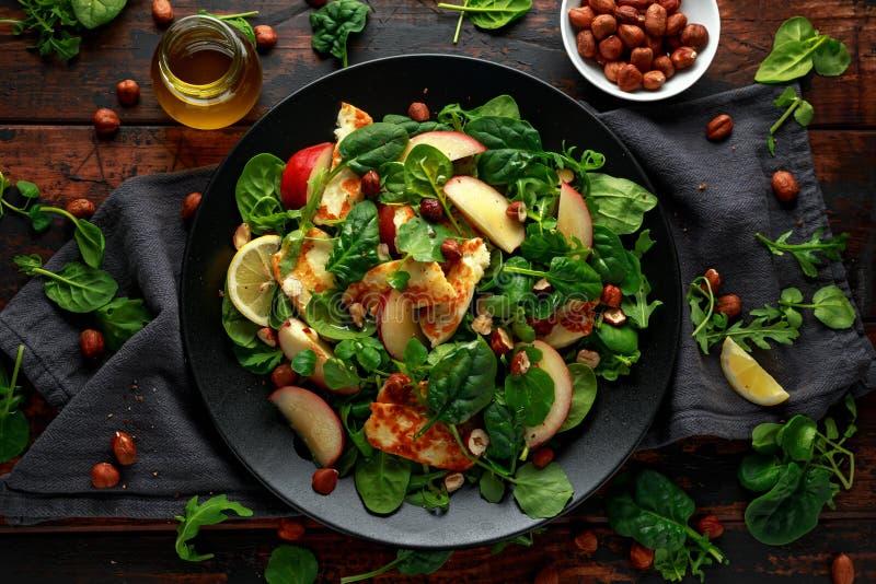 Geroosterde Halloumi-Kaassalade met perzikfruit, noten en spinazie, arugulamengeling Gezond voedsel stock foto's