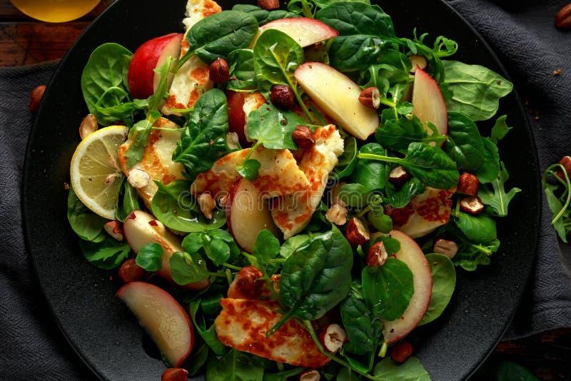 Geroosterde Halloumi-Kaassalade met perzikfruit, noten en spinazie, arugulamengeling Gezond voedsel stock afbeelding