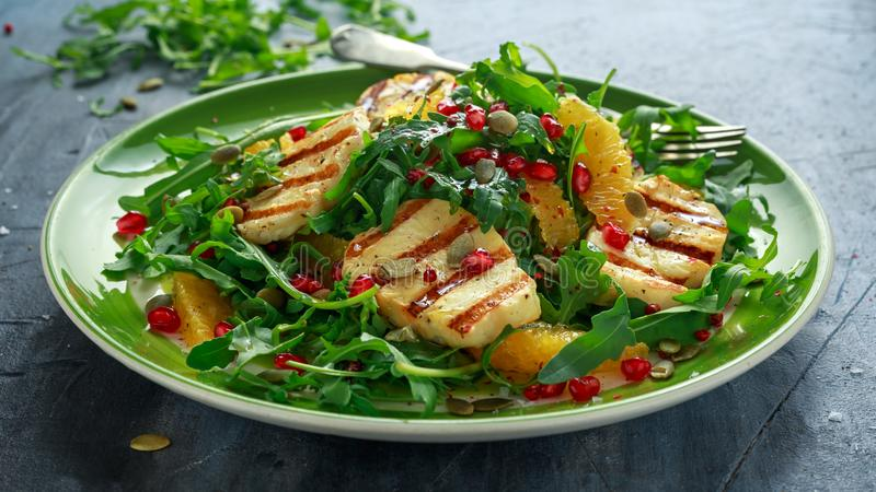 Geroosterde Halloumi-Kaassalade met sinaasappel, raketbladeren, granaatappel en pompoenzaad Gezond voedsel stock foto's