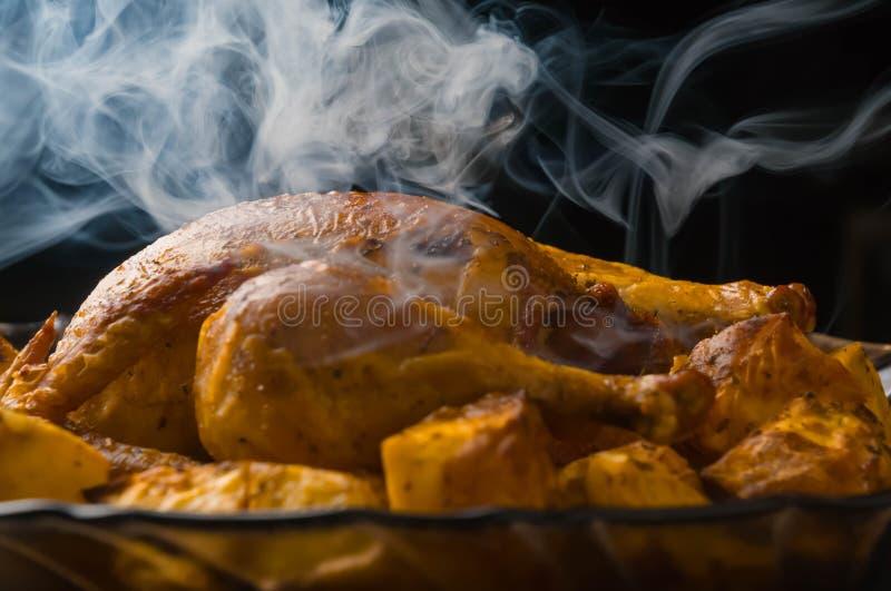 geroosterde kip en aardappels op glasplaat ood, gebakken gekookt gevogelte, rook, aroma royalty-vrije stock afbeelding