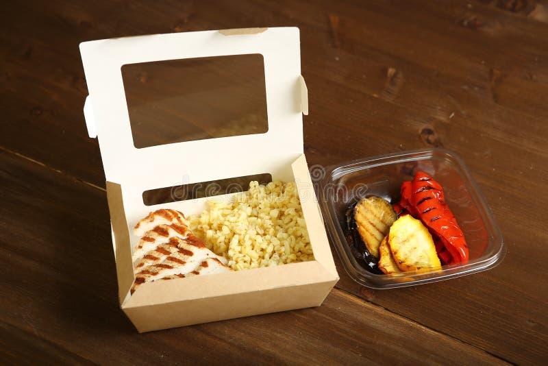 Geroosterde kip en groenten met plakken in twee containers stock afbeelding