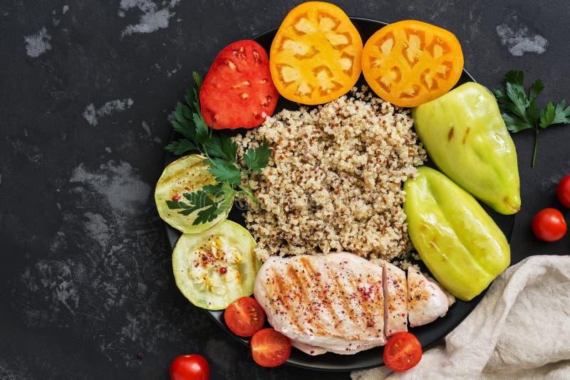 Geroosterde kip, quinoa en groenten, de kom van Boedha op een zwarte concrete achtergrond Gezond voedsel stock afbeeldingen