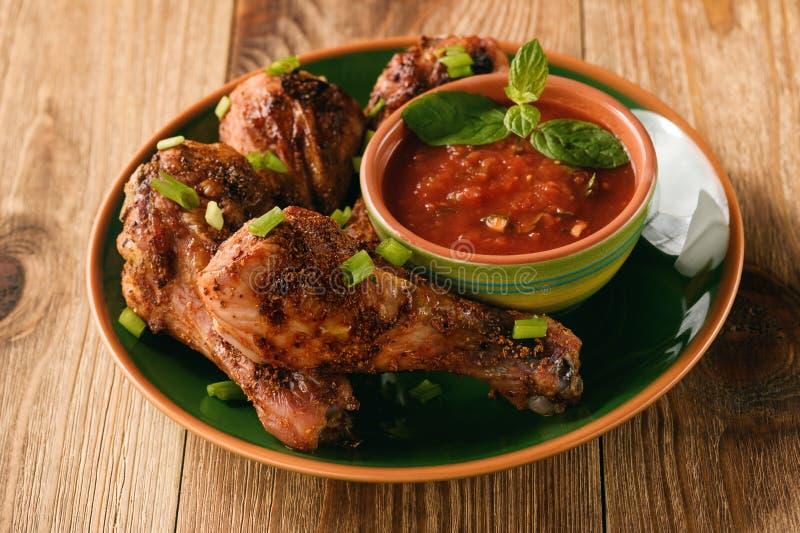 Geroosterde kippenbenen en tomatensaus op houten achtergrond stock afbeelding