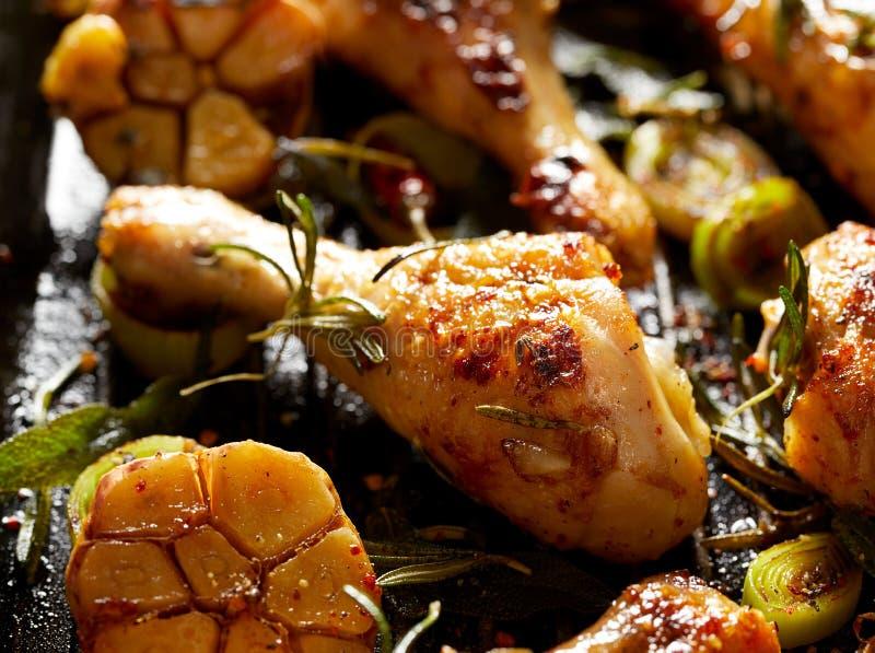 Geroosterde kippenbenen met aromatische kruiden en groenten op een barbecueplaat royalty-vrije stock foto's