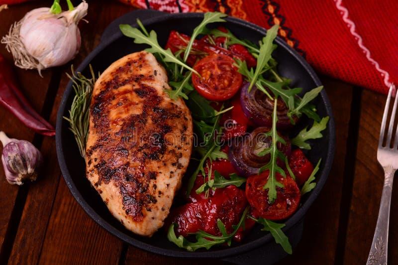 Geroosterde kippenborst met groene salade van arugula en groenten op een zwarte pan Houten rustieke achtergrond Hoogste mening stock afbeeldingen