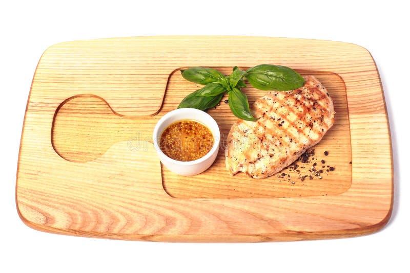 Geroosterde kippenborst op houten plaat met mosterd en basilicum Hoogste mening Geïsoleerd op wit stock fotografie