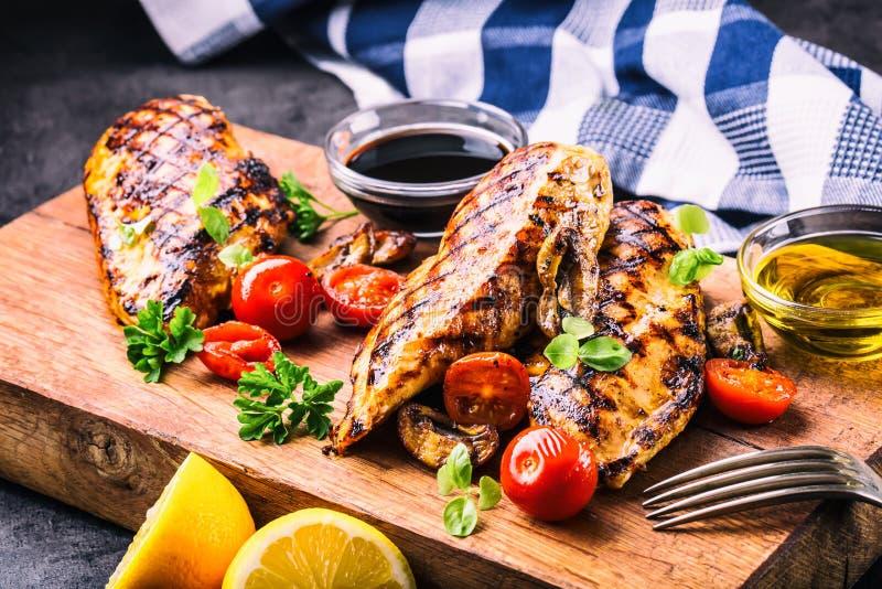 Geroosterde kippenborst in verschillende variaties met kersentomaten, paddestoelen, kruiden, besnoeiingscitroen op een houten raa royalty-vrije stock fotografie