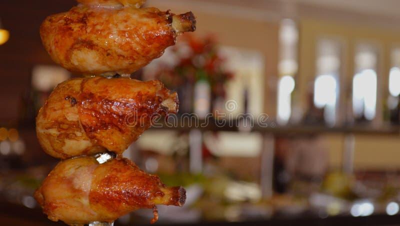 Geroosterde kippendijen op rotisserielapje vlees stock afbeelding