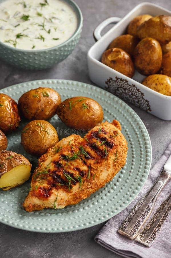 Geroosterde kippenfilet met aardappelen in de schil en de onderdompeling van de knoflookyoghurt royalty-vrije stock foto
