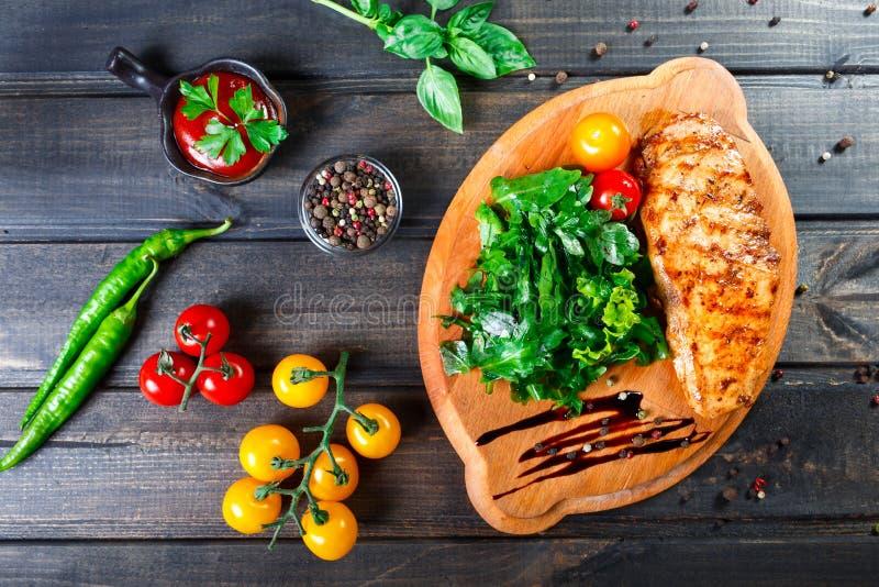 Geroosterde kippenfilet met verse groentesalade, tomaten en saus op houten scherpe raad Hete vleesschotels stock afbeelding