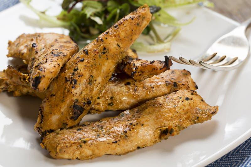 Geroosterde kippenstroken met zijsalade stock afbeelding