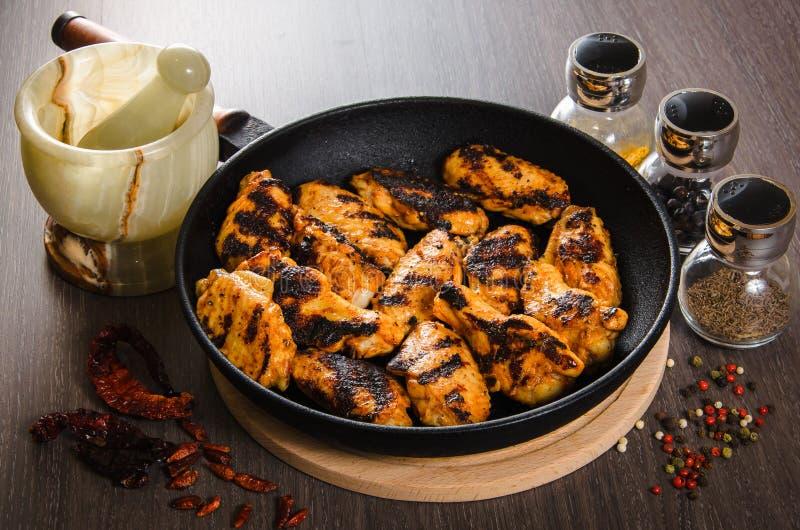 Geroosterde kippenvleugels in grill panwith kruiden, houten achtergrond royalty-vrije stock afbeeldingen
