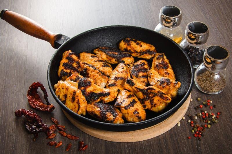 Geroosterde kippenvleugels in grill panwith kruiden, houten achtergrond royalty-vrije stock fotografie