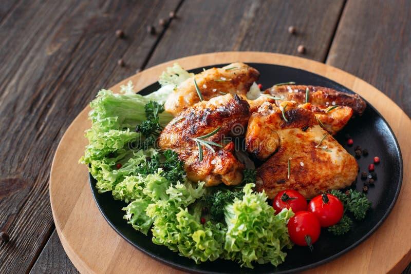 Geroosterde kippenvleugels met sla en tomaten royalty-vrije stock fotografie