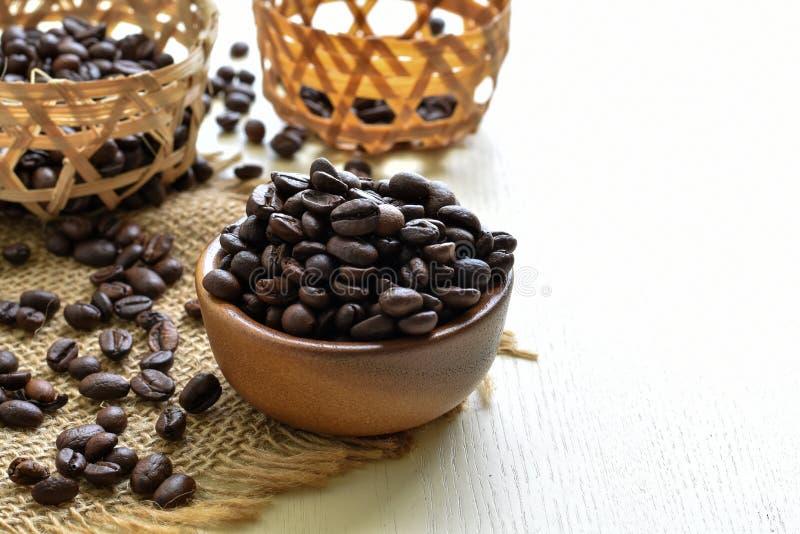 Geroosterde koffiebonen in een houten kop op jute royalty-vrije stock afbeelding