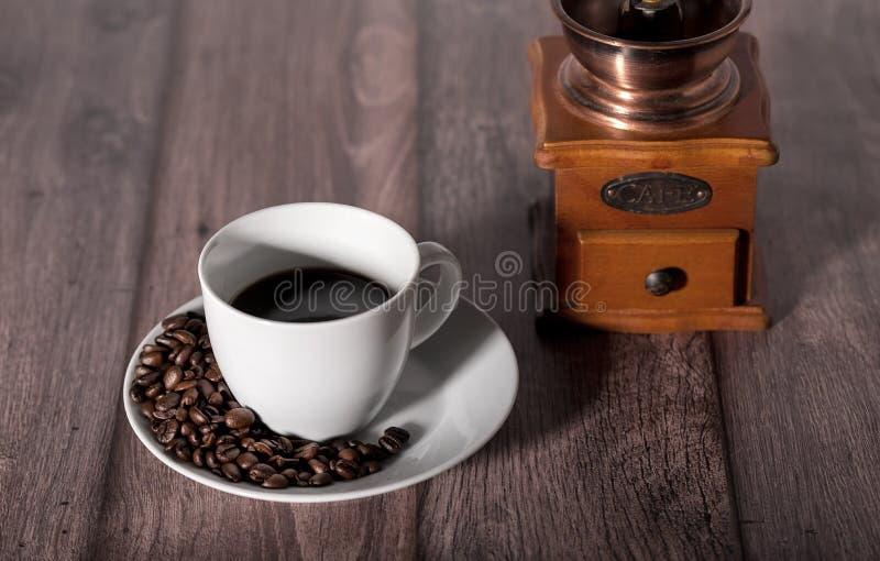 Geroosterde koffiebonen en kop van koffie op houten lijst stock fotografie