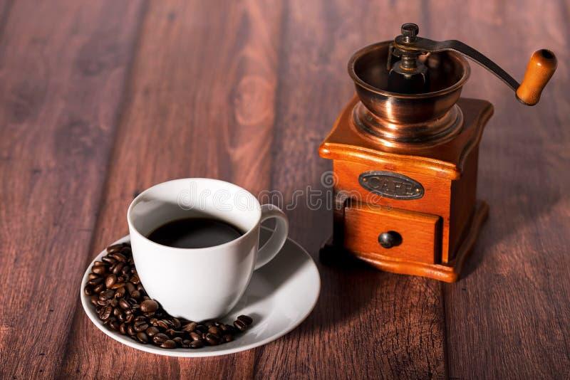 Geroosterde koffiebonen en kop van koffie op houten lijst stock foto's