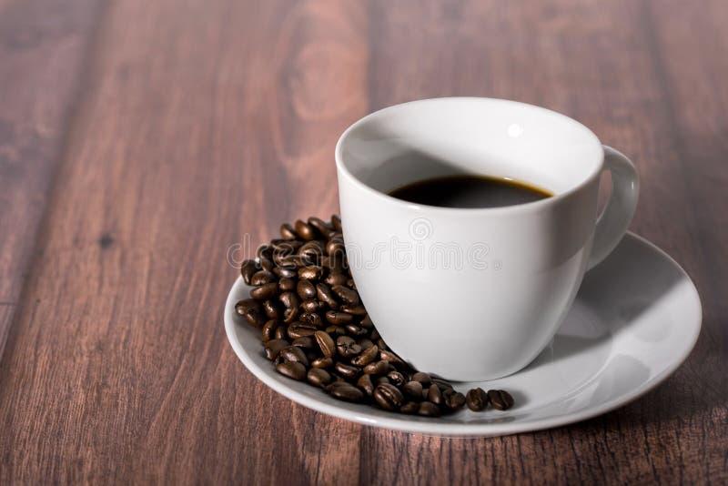 Geroosterde koffiebonen en kop van koffie op houten lijst royalty-vrije stock foto