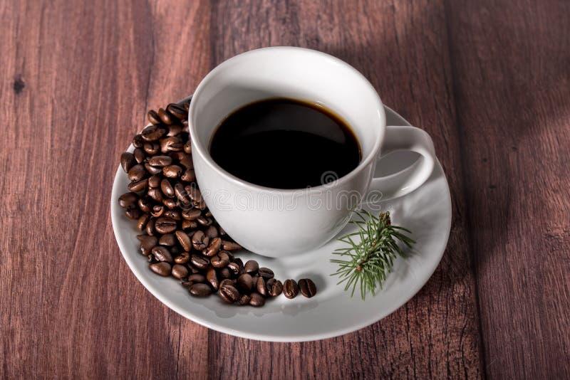 Geroosterde koffiebonen en kop van koffie op houten lijst royalty-vrije stock fotografie