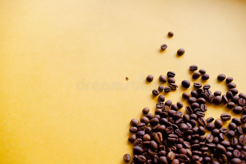 Geroosterde koffiebonen en meeneemkop hoogste mening Ambachtdocument de theekop op oranje vlakte als achtergrond lag De banner va stock afbeeldingen