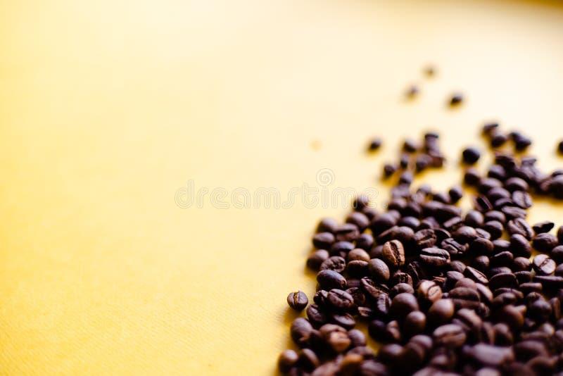Geroosterde koffiebonen en meeneemkop hoogste mening Ambachtdocument de theekop op oranje vlakte als achtergrond lag De banner va stock fotografie