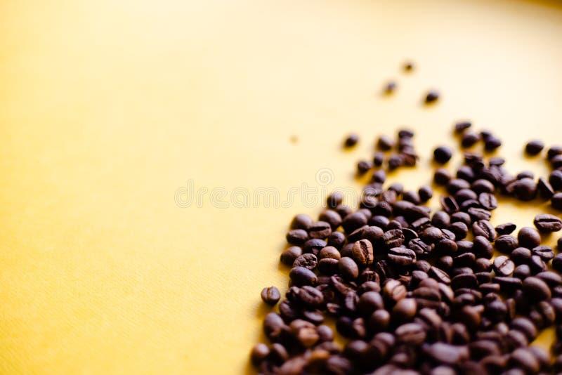 Geroosterde koffiebonen en meeneemkop hoogste mening Ambachtdocument de theekop op oranje vlakte als achtergrond lag De banner va stock foto