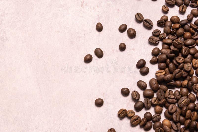 Geroosterde koffiebonen in massa op een lichtrose achtergrond donkere cofee geroosterde het aromakoffie van het korrelaroma, de n stock foto