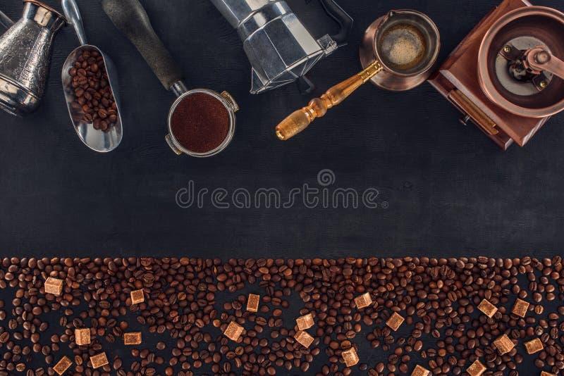 Geroosterde koffiebonen met bruine suiker en diverse koffiezetapparaten en molens op zwarte stock foto