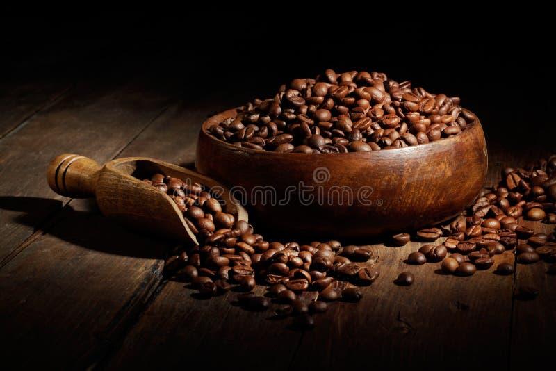 Geroosterde koffiebonen met lepel en kom op oude houten lijst stock foto's