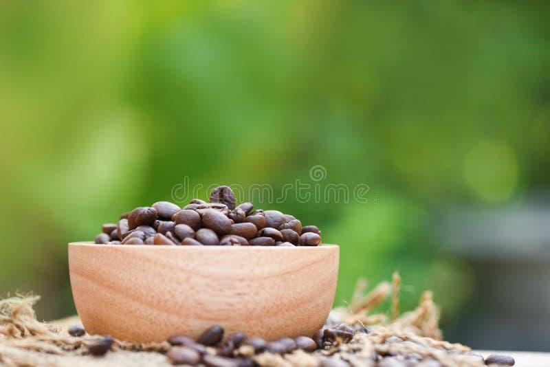 Geroosterde koffiebonen op houten kom en zak/Close-upkoffiebonen op aard groene achtergrond stock foto