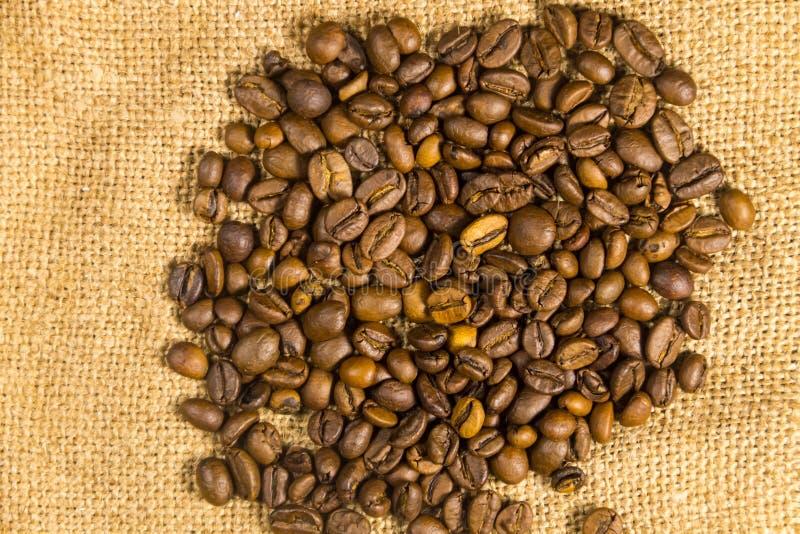Geroosterde koffiebonen op jute geweven achtergrond royalty-vrije stock afbeelding