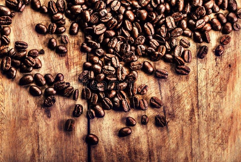 Geroosterde koffiebonen op uitstekende lijst. Koffie op houten grunge royalty-vrije stock afbeeldingen